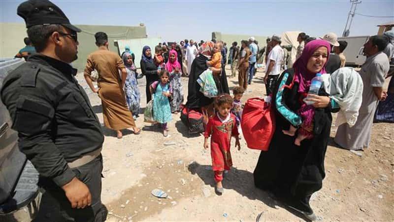 Yezidi Women, Men and Children entering an IDP Camp
